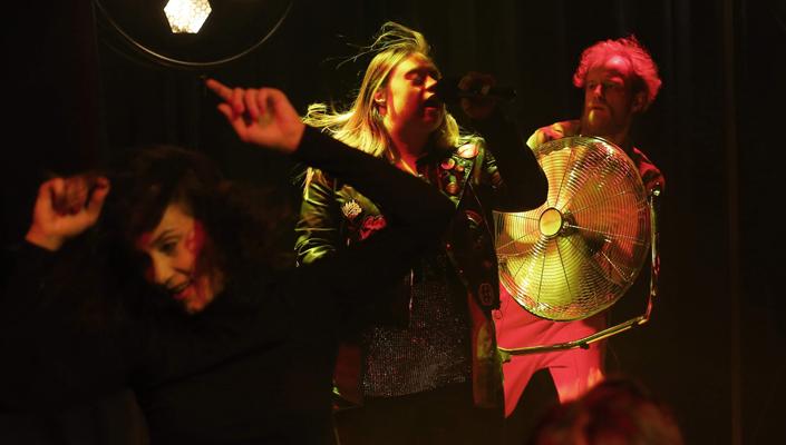 Fotografia z przedstawienia teatralnego: na zdjęciu widać trzy postacie, każda widziana mniej więcej od pasa w górę. Z przodu kobieta ubrana na czarno, w tanecznej pozie, z rękami nad głową, uśmiecha się. Za nią kobieta z zespołem Downa, ma długie, rozwiane włosy i kolorowe ubranie, prawdopodobnie porusza się w rytm muzyki. Za kobietą stoi mężczyzna, trzymający duży, elektryczny wiatrak, skierowany na nią. Mężczyzna jest oświetlony czerwonym światłem reflektora znad sceny.