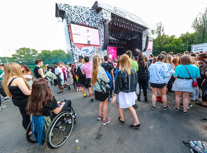 W tle widoczna scena festiwalowa, widziana z boku, i towarzyszące jej telebimy, nad sceną napis Orange Warsaw Festiwal. Przed sceną tłum młodych ludzi w letnich strojach, w tłumie, na pierwszym planie, po lewej stronie, dziewczyna na wózku aktywnym. Wszyscy patrzą w kierunku sceny, widać ich plecy.