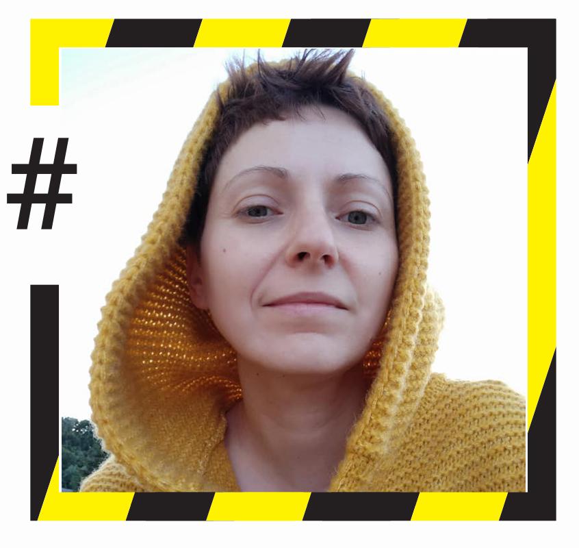 """Kolorowe zdjęcie w kwadratowej, czarno-żółtej ramce, przypominającej taśmę ostrzegawczą. Z lewej strony ramka jest przerwana a w przerwie znajduje się czarny znaczek """"hasztag"""". Na zdjęciu młoda, krótkowłosa kobieta w żółtym swetrze z kapturem narzuconym na głowę. Kobieta patrzy prosto w obiektyw, delikatnie się uśmiecha."""